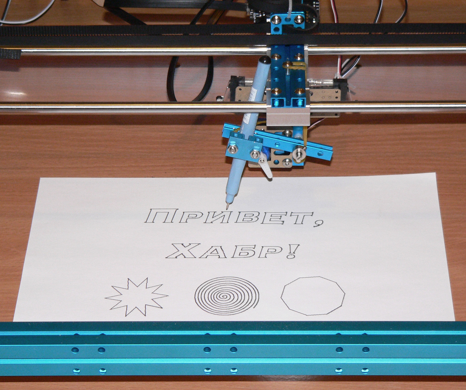 Photo of a plotter with a sheet of paper in which a drawing