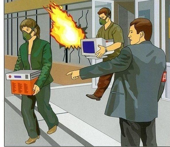 люди с компьютером и документами организованно покидают горящее здание