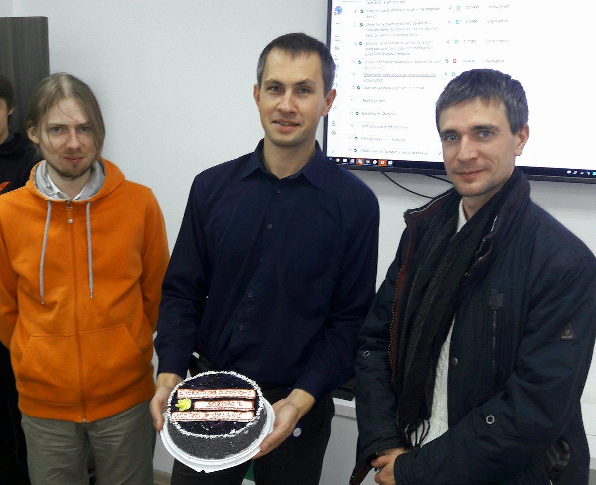 Автор (в оранжевом худи) и его коллеги с тортиком. На тортике написано «всё отлично» на 3 языках