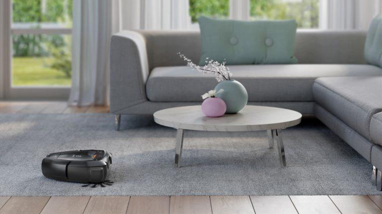Pure i9 чистит ковер и моет пол вокруг стола и дивана.