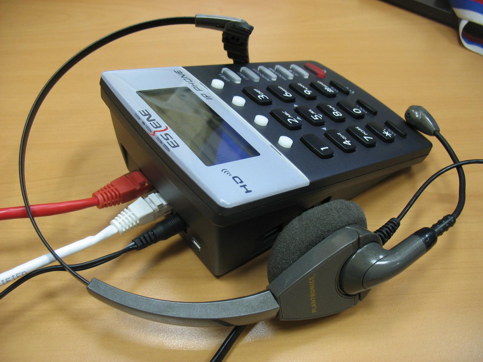 Вид телефона на столе с гарнитурой