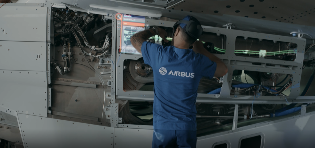 An Airbus engineers uses a HoloLens headset to perform maintenance on an aircraft.