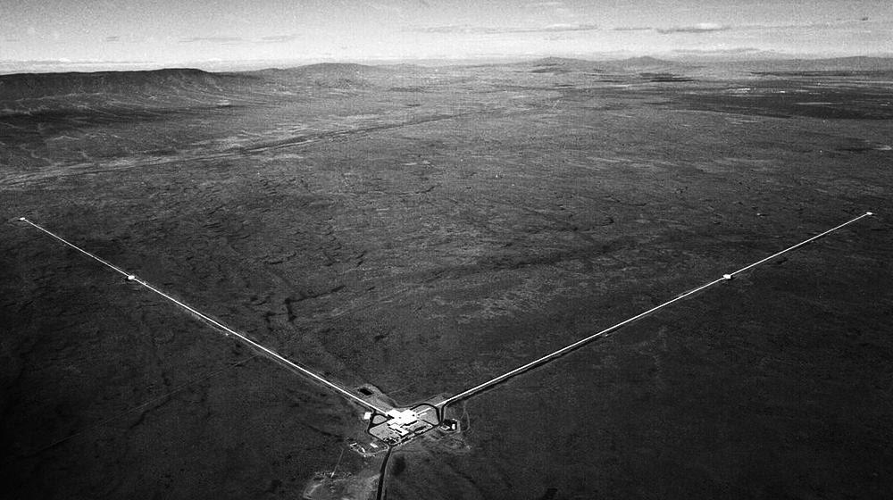 Детектор LIGO в г. Хэнфорде, штат Вашингтон, имеет две длинные стрелы, расположенные под прямым углом. Лазеры внутри каждой стрелы измеряют относительную разницу длин каждой из стрел при прохождении гравитационной волны