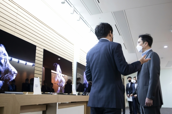 Вице-председатель Samsung Ли Чжэ Ён (справа) проверяет образцы панелей QD-OLED от Samsung Display
