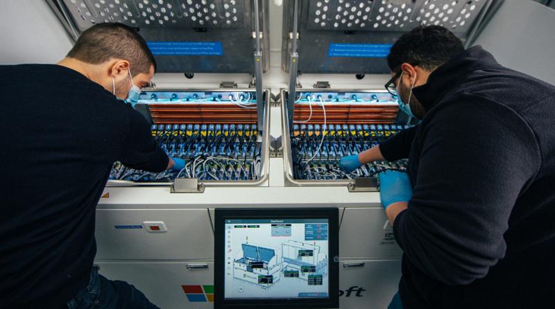 Иоаннис Манусакис, главный инженер-программист в Azure (слева), и Хусам Алисса, главный инженер по аппаратному обеспечению в группе Microsoft по расширенной разработке центров обработки данных (справа), осматривают внутреннюю часть резервуара двухфазного иммерсионного охлаждения