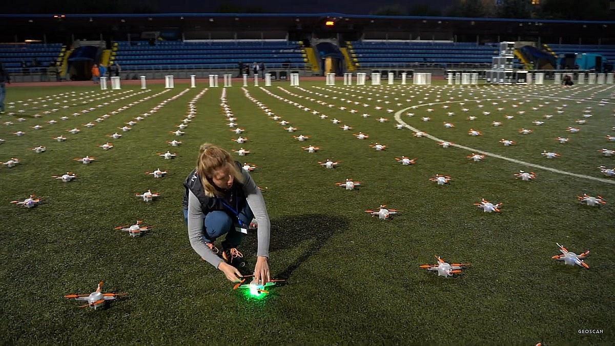 Команда расставляет дроны на поле перед началом шоу