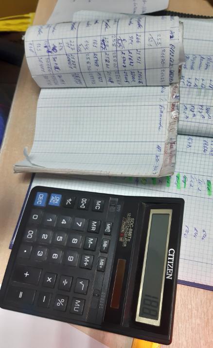 Настольный калькулятор и журналы на столе диспетчера