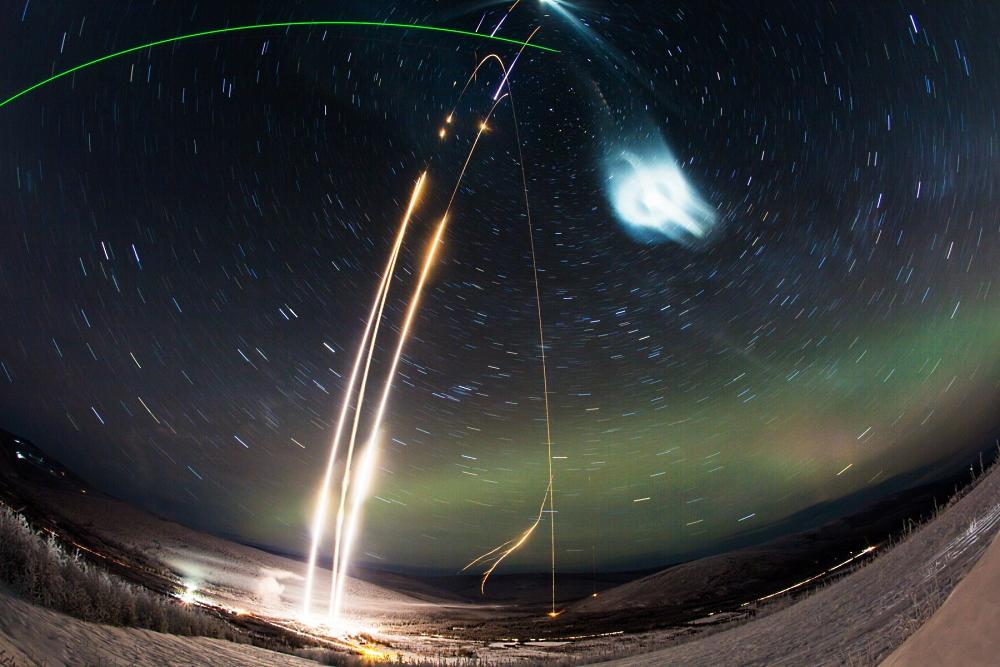 Две ракеты с трассерами для наблюдения за ветром на высоте, одна ракета с водой. Зеленый луч - лидар (лазерный радар). Фото NASA's Wallops Flight Facility/Poker Flat Research Range/Zayn Roohi