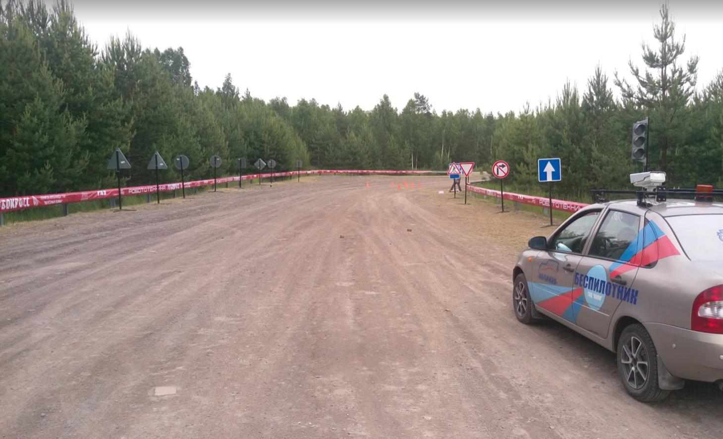 Трасса с однорядным барьером на котором закреплены баннеры, со знаками и БПТС команды НАМИ