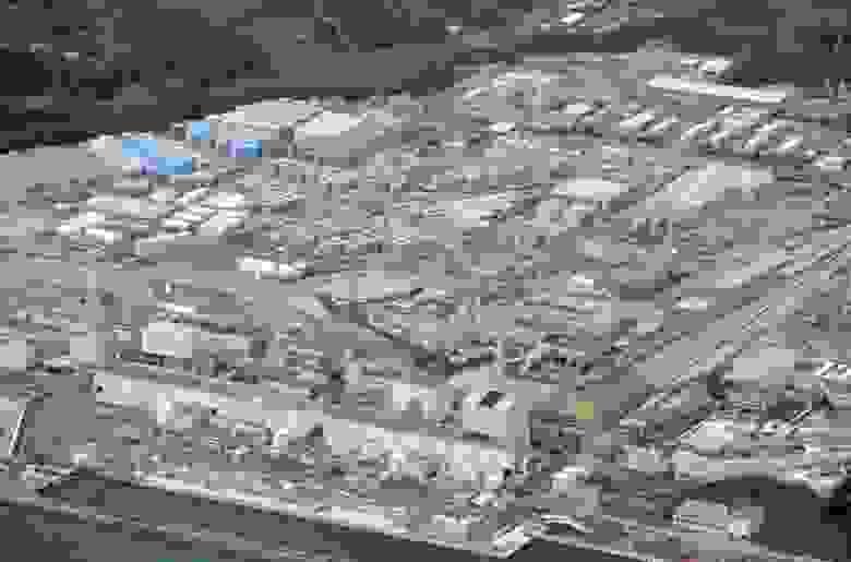 Фото площадки АЭС Фукусима Дайчи, 2015 г. 4 энергоблока внизу, а в середине кадра видны многочисленные баки для хранения загрязненной воды.