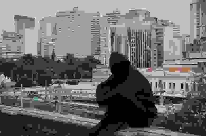 Грустный чувак в капюшоне на фоне сурового мегаполиса – куда ж нам без него, если мы пишем об анонимности – вольная интерпретация стоковой фотографии. Фото: Daniel Monteiro // Unsplash (CC BY-SA 4.0)