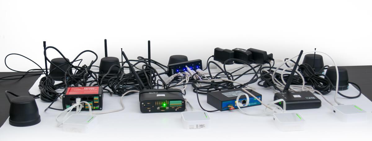 Все роутеры, разом подключенные на столе. Целая куча проводов и антенн.